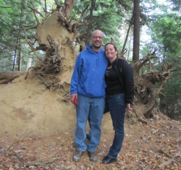 Jay and Diana in fron tof uprooted tree with rock in roots