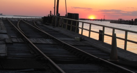 sun is setting over the water and the rail yard in cape charles